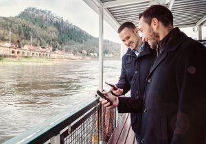 Nicht jeder Verkehrsverbund hat auch Fahrten zu Wasser in seinem Repertoire. Der VVO schon: Auf der Fähre in Königstein besprechen Oliver Horeni, Tarif-Experte beim VVO (rechts), und Sascha Heiser, verantwortlicher Projektleiter bei der Dresdner Verkehrsbetriebe AG, die Vorzüge eines intuitiven Check-In/Check-Out-Systems für Gelegenheitsfahrer.